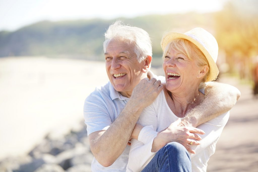 Happy elder couple laughing together at the beach