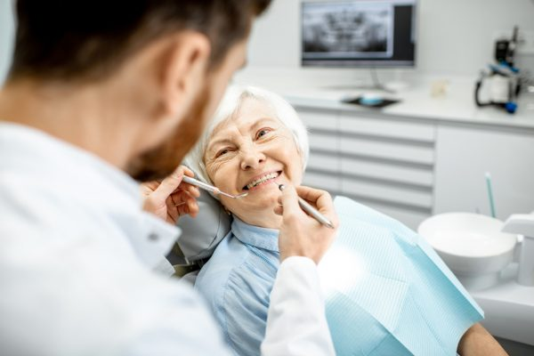 older patient smiling with her dentist